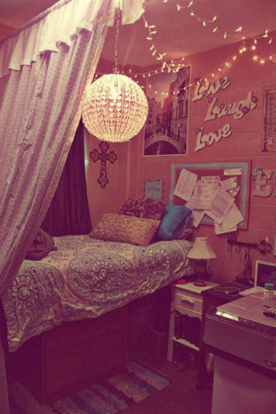 An image of a pink, pattern filled dorm room with a disco ceiling light.