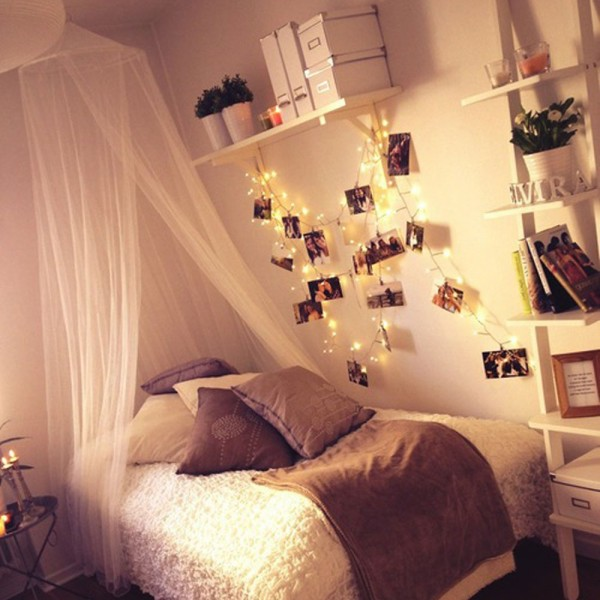 Purple canopy bed dorm room with hanging lights.